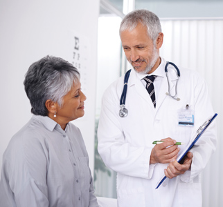 Male doctor showing information to older woman patient in exam room